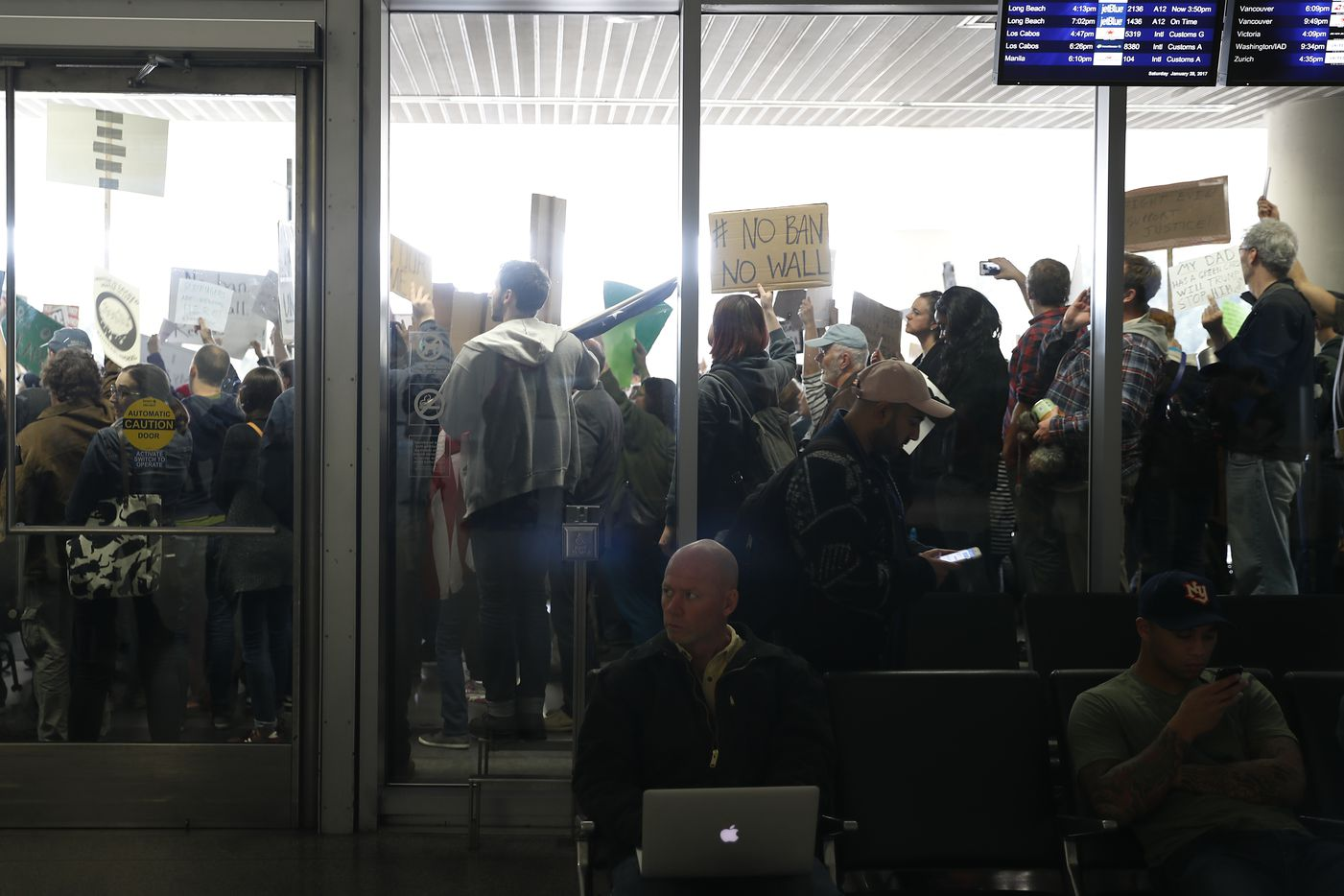 People at the international arrival terminal as demonstrators hold signs against a ban on Muslim immigration at San Francisco International Airport on January 28, 2017 in San Francisco, California.