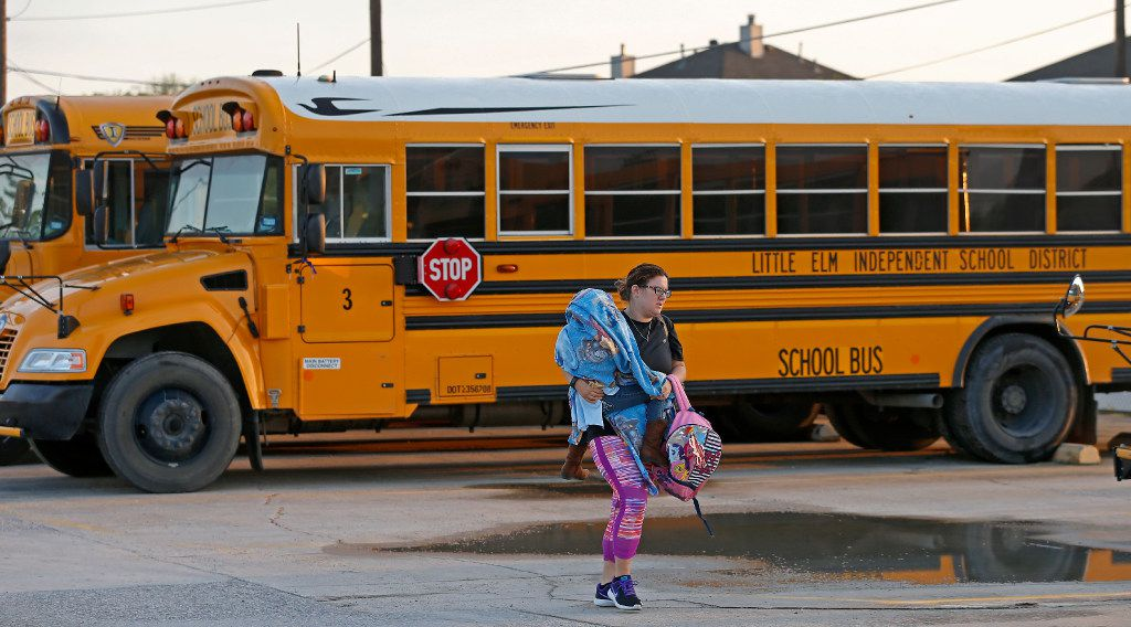 Bus driver Jennifer Alaniz carrying her 5-year-old daughter Sadie leaves the Little Elm ISD Maintenance Department lot in Little Elm, Texas, Monday, March 27, 2017. Last night's hailstorm damaged 35 of the districtÕs 48 buses and caused the 2 and half hour delay in the morning. (Jae S. Lee/The Dallas Morning News)
