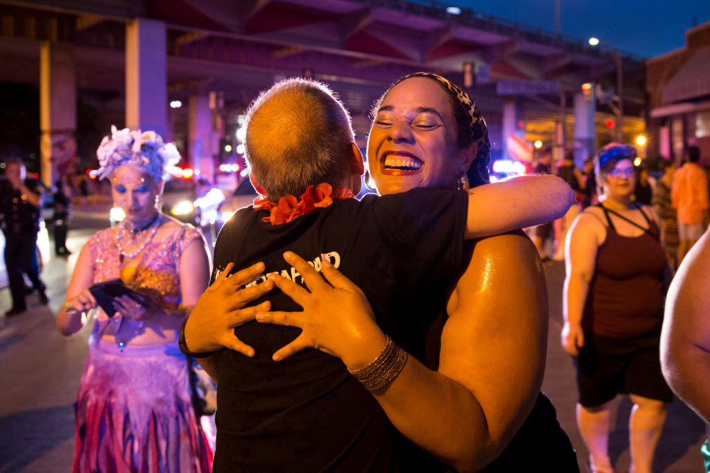 Mike Keller (back to camera), of Dallas, and Stephanie St. John (center right), of Addison,  Texas embrace each other during the Queer Bomb Dallas procession march though Deep Ellum streets on June 25, 2016 in Dallas. (Ting Shen/The Dallas Morning News)