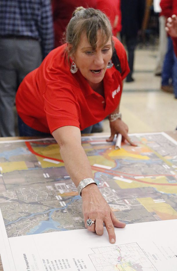 Lori Swim of McKinney points to a map as she makes a point while area residents met to look at maps of the latest iteration of the proposed bypass for Highway 380 at Rogers Middle School in Prosper.