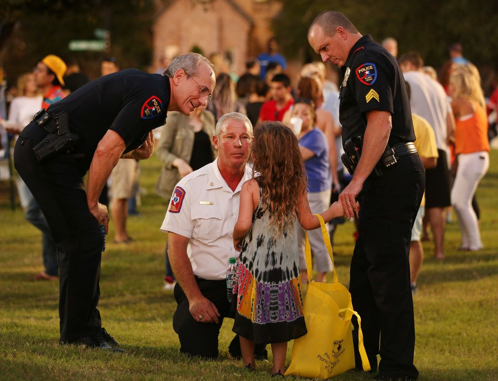 Plano Police Chief Greg Rushin (left), Plano Fire Chief Sam Greif (middle), and Plano police Sgt. Wes Gerig help a lost girl during National Night Out in the Kings Ridge neighborhood.