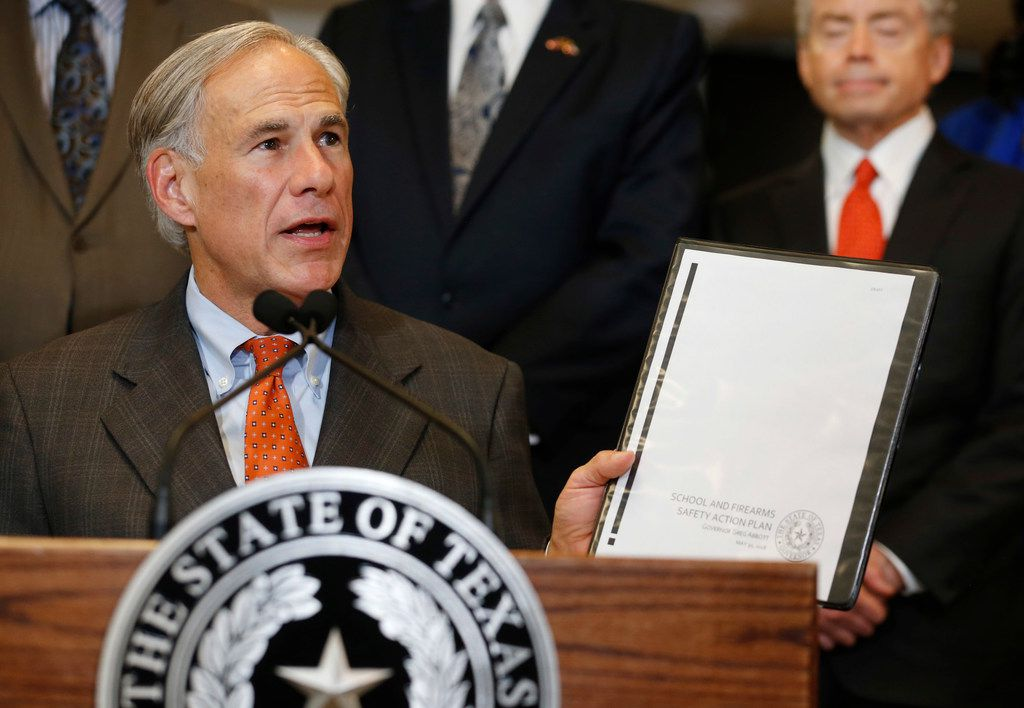 Governor Greg Abbott holds up his School and Firearm Safety Action Plan during a press conference at Dallas ISD Headquarters Wednesday, May 30, 2018.