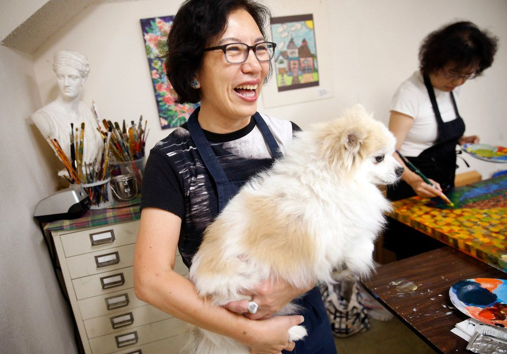 Local artist Jenney Chang laughs while talking about the artistic skills of her Pomeranian, Bentley, in her Plano home studio on Aug. 11, 2019. She once integrated his paw prints into a painting of flowers which hangs in her studio.