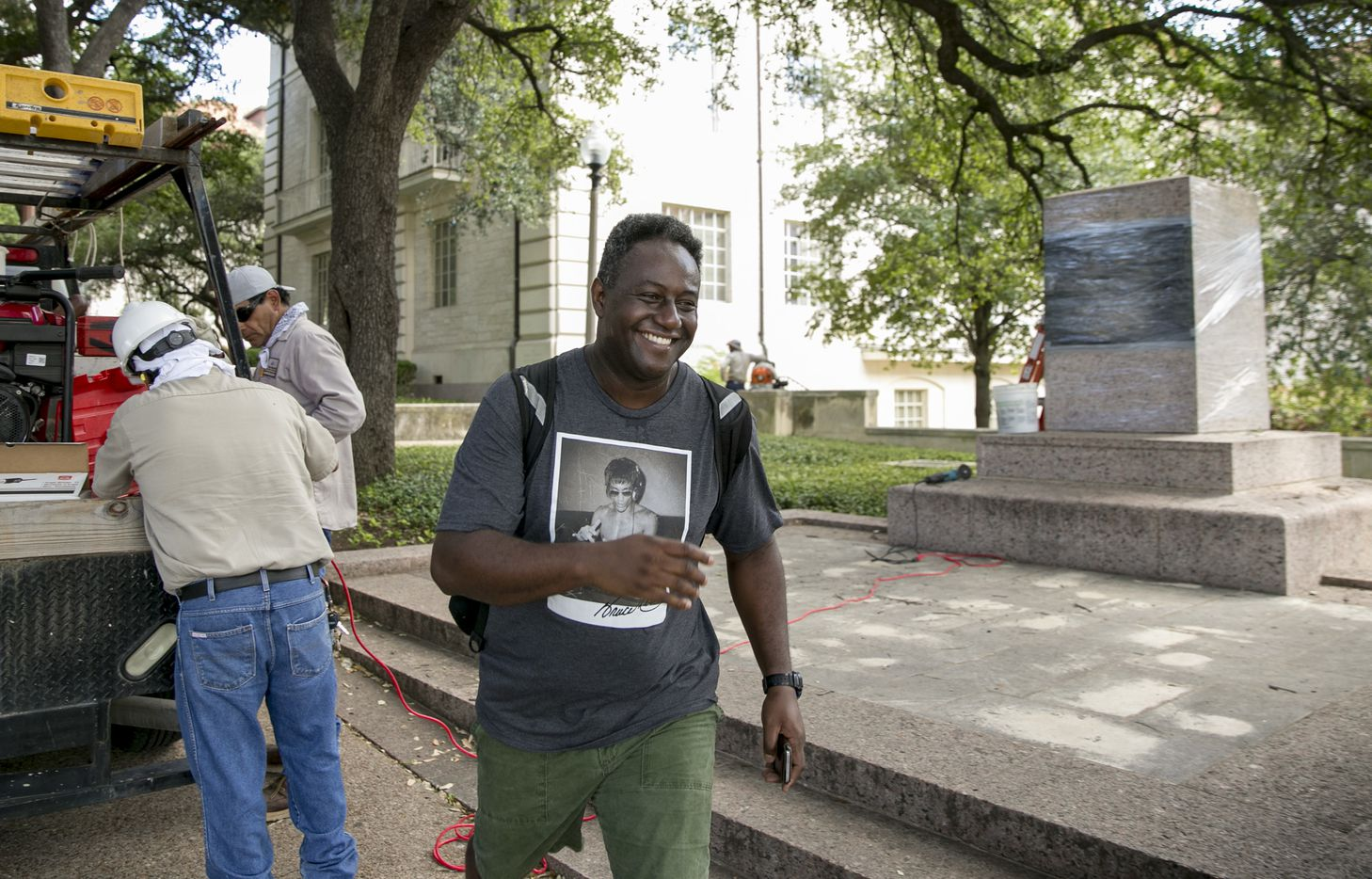 """Clayton Souza smiles as he walks past an empty pedestal where a statue of Confederate Postmaster John Reagan was displayed on the UT campus Monday, Aug. 21, 2017.  """"It's a great moment for the U.S., and for Texas,"""" Souza said."""