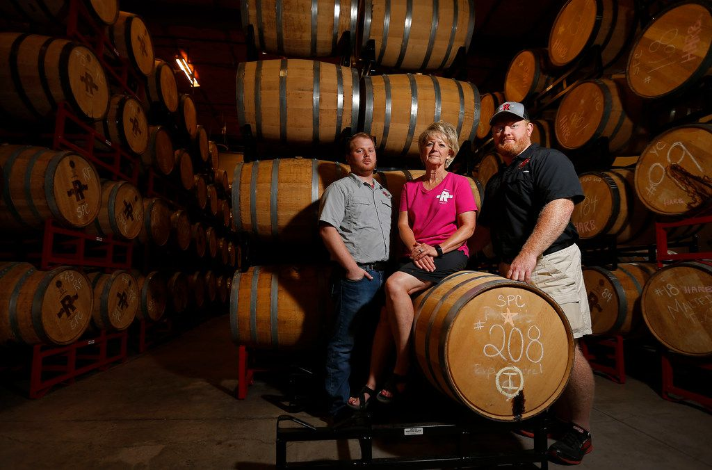 From left, Co-owners Robert Likarish, Marcia Likarish and Jonathan Likarish pose for a photograph with barrels of whiskey in the distillery at Ironroot Republic Distilling in Denison, Texas, Tuesday, June 12, 2018.  (Jae S. Lee/The Dallas Morning News)