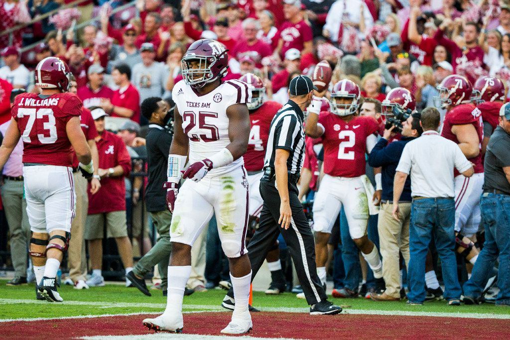 Texas A&M linebacker Tyrel Dodson (25) walks off the field as Alabama quarterback Jalen Hurts (2) celebrates after scoring on a 37-yard touchdown run during the second half of an NCAA college football game, Saturday, Oct. 22, 2016, in Tuscaloosa, Ala. (Smiley N. Pool/The Dallas Morning News)