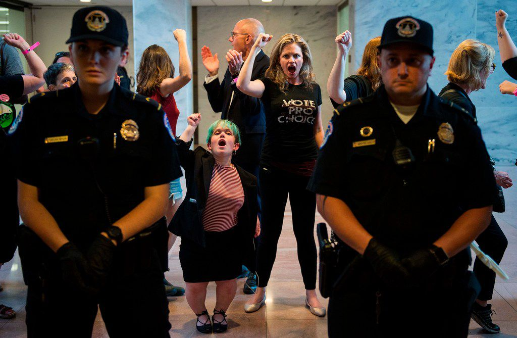 """TOPSHOT - Police look on as protesters are arrested in the Senate Hart building during a rally against Supreme Court nominee Brett Kavanaugh on Capitol Hill in Washington, DC on October 4, 2018. - Top Republicans voiced confidence Thursday that Brett Kavanaugh will be confirmed to the US Supreme Court this weekend, as they asserted that an FBI probe had found nothing to support sex assault allegations against Donald Trump's nominee.""""Judge Kavanaugh should be confirmed on Saturday,"""" Senator Chuck Grassley of Iowa, the chairman of the Senate Judiciary Committee, told reporters. (Photo by ANDREW CABALLERO-REYNOLDS / AFP)ANDREW CABALLERO-REYNOLDS/AFP/Getty Images"""