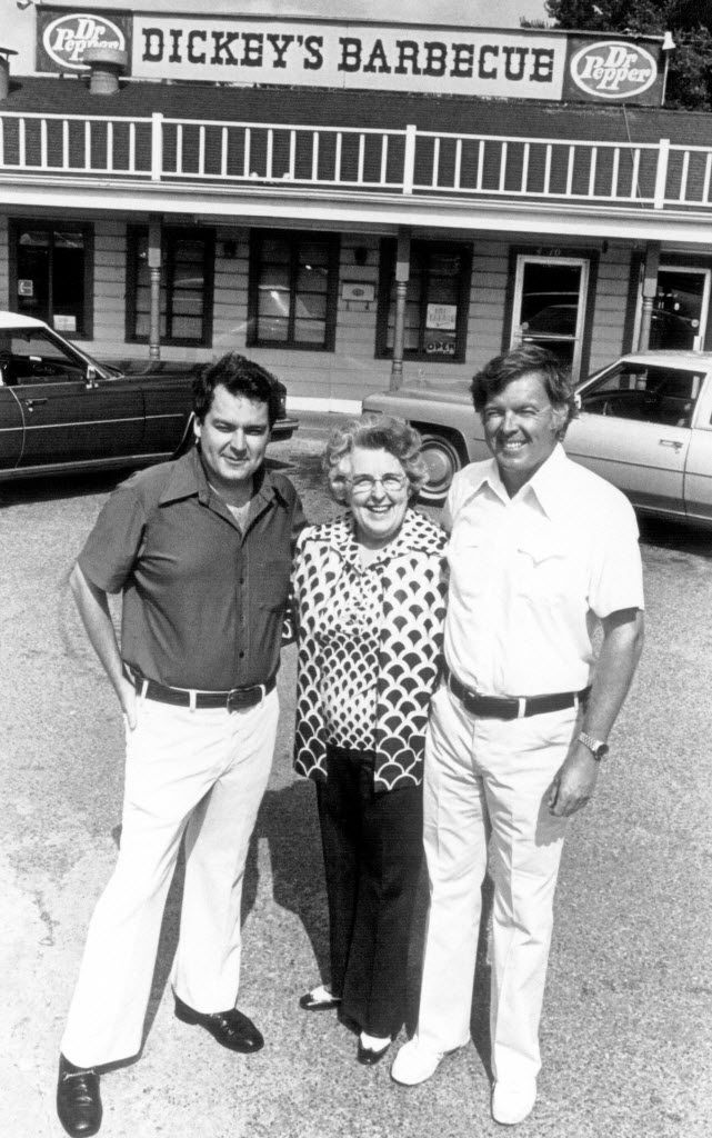 "Roland Dickey (left) and Travis ""TD"" Dickey Jr. stood with their mother, Ollie Dickey, in front of the original Dickey's Barbecue Pit on North Central Expressway and Henderson Avenue in 1976."
