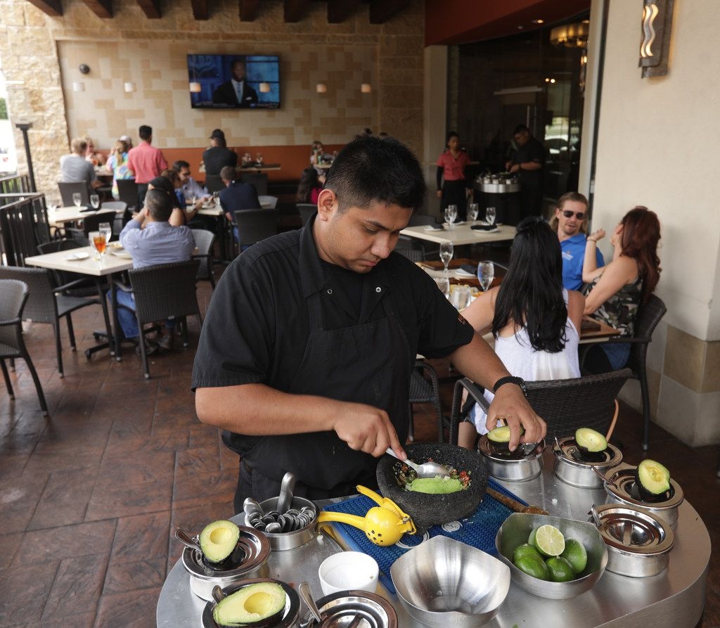 Christian Santiago makes guacamole on the patio at Mi Dia From Scratch in Plano, TX, on Jun. 7, 2019. (Jason Janik/Special Contributor)