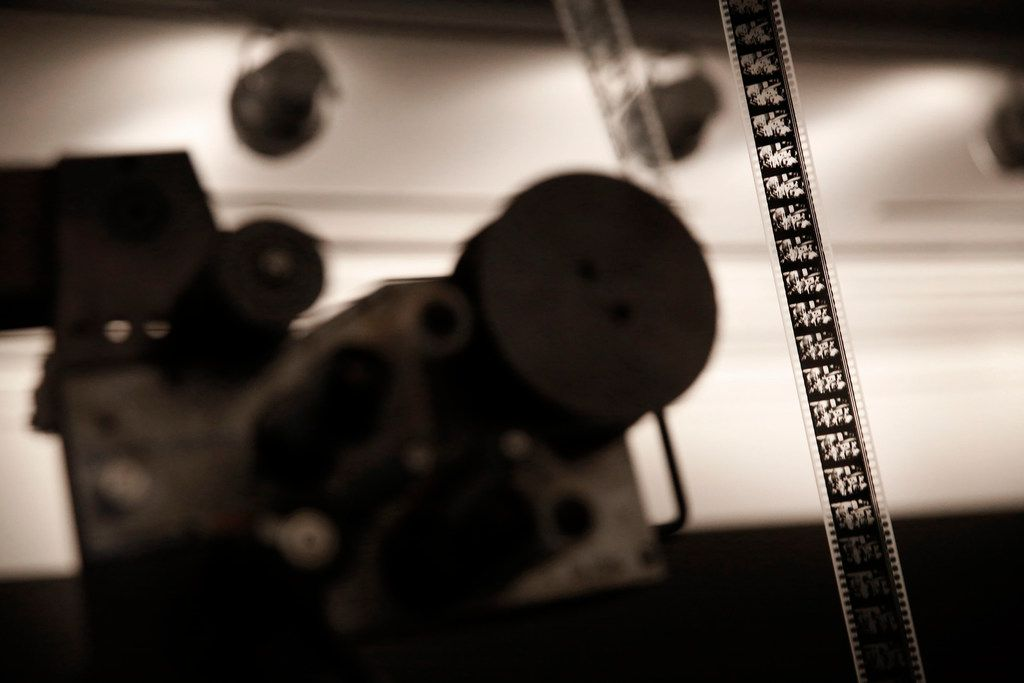 "Film moves through a 35 mm projector as part of an art exhibition called ""ARK."""