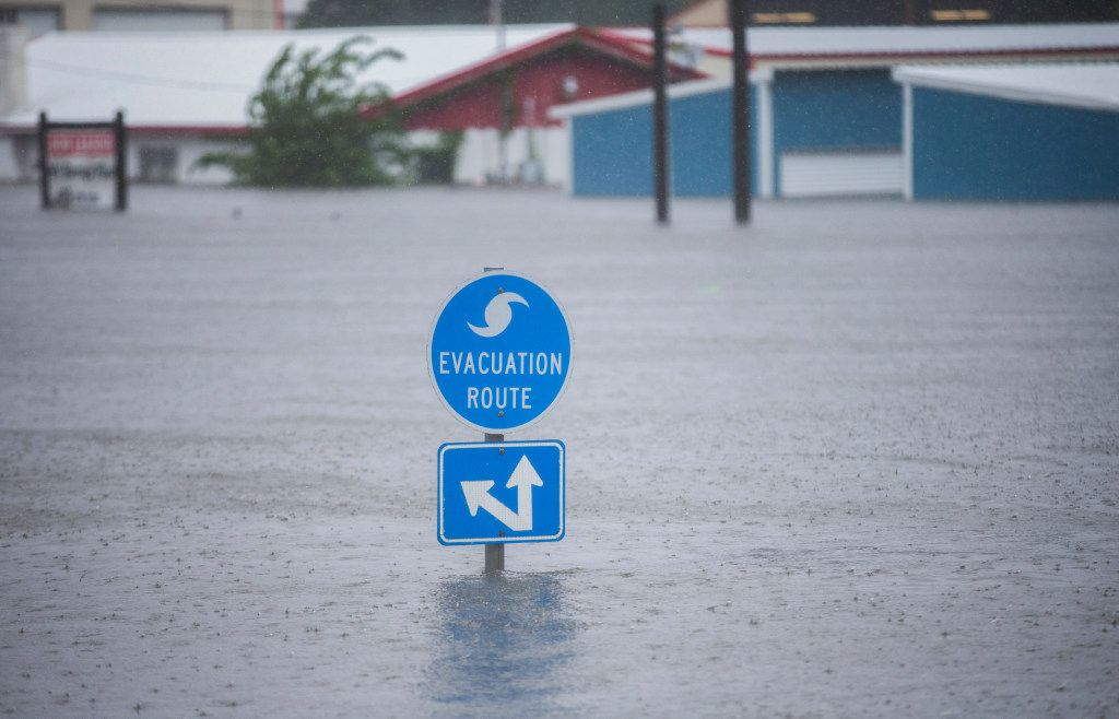 A hurricane evacuation route sign on Highway 96 hovered over floodwaters from Hurricane Harvey in late August in Lumberton in southeast Texas. (Ashley Landis/Staff Photographer)