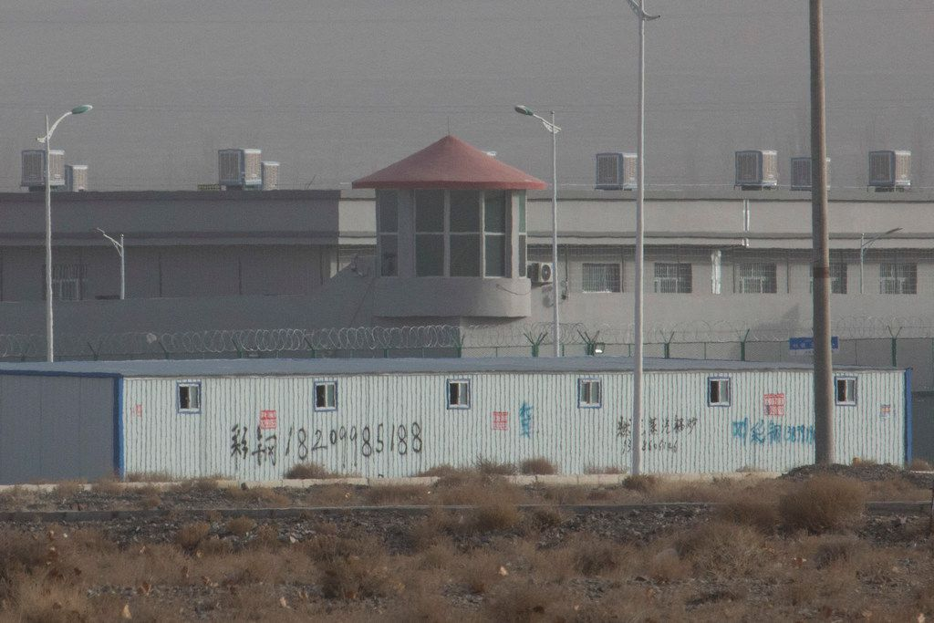 In this Monday, Dec. 3, 2018, photo, a guard tower and barbed wire fences are seen around a facility in the Kunshan Industrial Park in Artux in western China's Xinjiang region. This is one of a growing number of internment camps in the Xinjiang region, where by some estimates 1 million Muslims are detained, forced to give up their language and their religion and subject to political indoctrination. Now, the Chinese government is also forcing some detainees to work in manufacturing and food industries. Some of them are within the internment camps; others are privately owned, state-subsidized factories where detainees are sent once they are released.