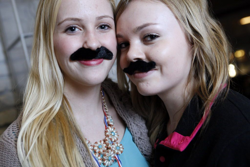 Two hostesses show off their fake mustaches purchased from the vending  machine in Smoke's entrance.
