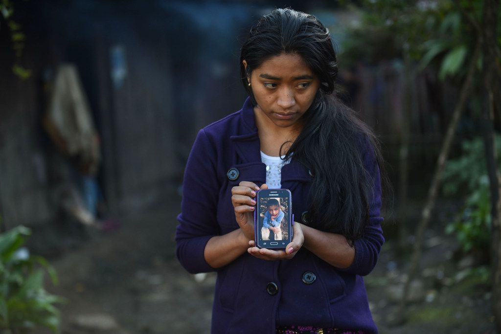 Catarina Gomez Lucas, sister of eight-year-old migrant Felipe Gomez, who died in a medical center in Alamogordo, New Mexico, on December 24 while in custody of U.S. Customs and Border Protection officers, shows a picture of her brother on a mobile phone outside her house in Yalambojoch village, Nenton municipality, Huehuetenango department, Guatemala.