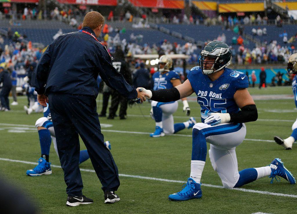 NFC head coach Jason Garrett, of the Dallas Cowboys, shakes hands with tackle Lane Johnson (65), of the Philadelphia Eagles, before the NFL Pro Bowl football game Sunday, Jan. 27, 2019, in Orlando, Fla. (AP Photo/Mark LoMoglio)
