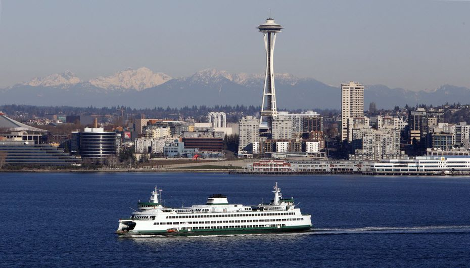 With the Cascade Mountains as a backdrop, a ferry sets sail across Elliott Bay out of Seattle and past the city's iconic Space Needle.