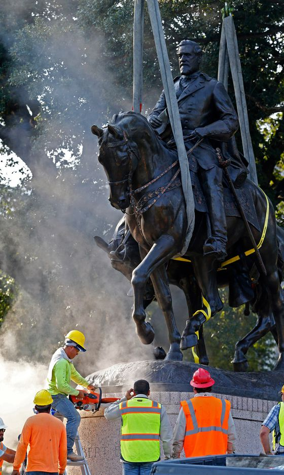 Workers cut the Robert E. Lee statue off of its base for its removal at Robert E. Lee Park in Dallas on Sept. 14, 2017.