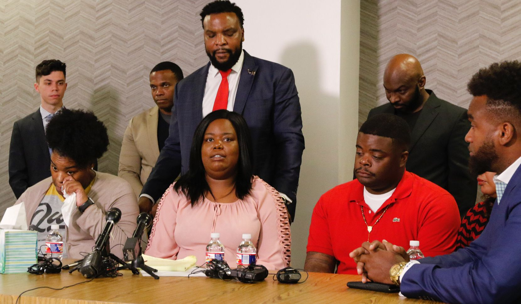 Amber Carr, left, wipes a tear as her sister Ashley Carr, center, talks about their sister, Atatiana Jefferson, their brother, Adarius Carr, right and attorney Lee Merritt, standing, listen during a press conference at 1910 Pacific on Monday morning, October 14, 2019 in downtown Dallas. Atatiana Jefferson, a 28-year-old black woman, was shot and killed in her home by a white Fort Worth police officer during a welfare check.