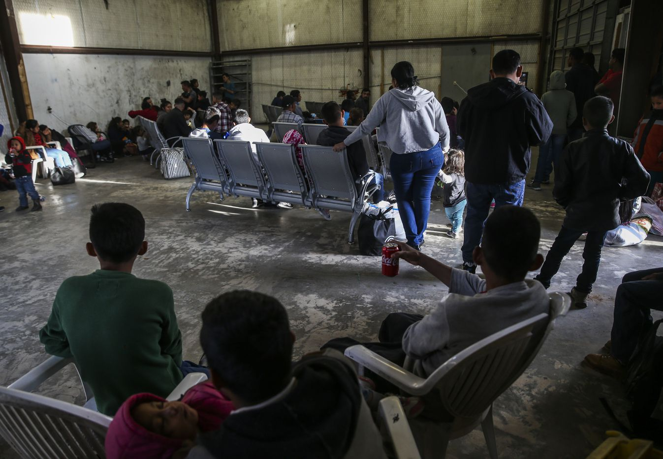 A group of people, mostly Central American migrant asylum seekers, wait in the waiting room of a Tornado Bus station in El Paso, Texas, on Saturday, March 30, 2019.