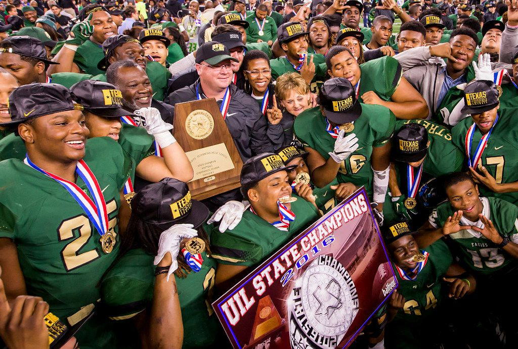 DeSoto head coach Todd Peterman clutches the championship trophy as he celebrates with his players after a victory over Cibolo Steele in the UIL Class 6A Division II state football championship football game at AT&T Stadium on Saturday, Dec. 17, 2016, in Arlington. DeSoto won the game 38-29. (Smiley N. Pool/The Dallas Morning News)