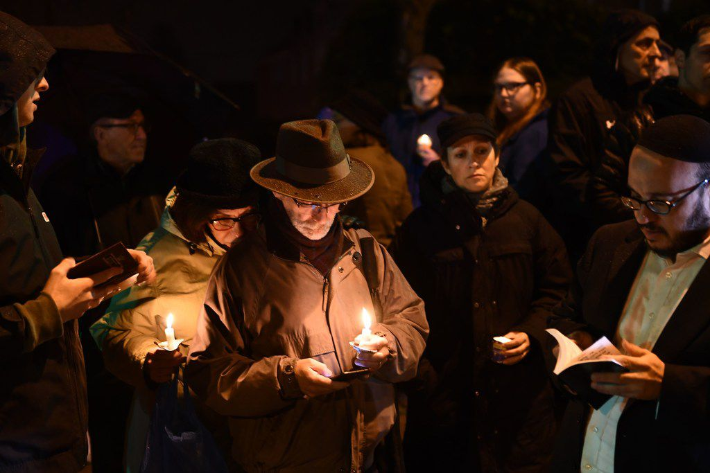 People hold candles outside the Tree of Life Synagogue after a shooting there left 11 people dead in the Squirrel Hill neighborhood of Pittsburgh on Saturday. (Brendan Smialowski/Getty Images)