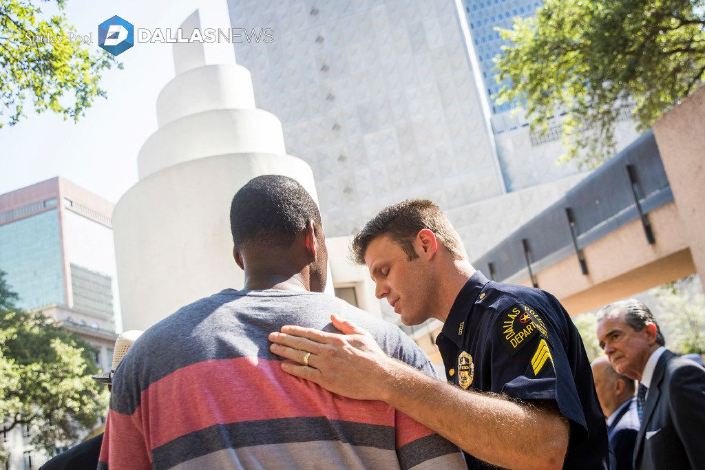 Dallas police Sgt. Dan Mosher comforts Odell Edwards, the father of Jordan Edwards, a 15-year-old who was killed by a Balch Springs police officer in April, during a day of remembrance for last year's police ambush organized by Faith Forward Dallas at Thanks-Giving Square on July 7, 2017, in Dallas.
