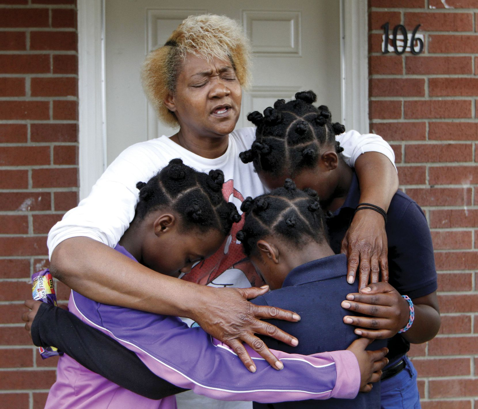 Paula Wooten prays with her grandchildren A'avryanna Wooten (left), 10, I'ivryanna Wooten (center), 9, and R'reanna Wooten, 11, in front of their Dallas Housing Authority apartment before they walk to school at George W. Carver Creative Arts Learning Center.
