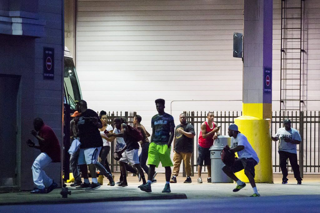 Bystanders run for cover after shots fired at a Black Lives Matter rally in downtown Dallas on Thursday, July 7, 2016. Dallas protestors rallied in the aftermath of the killing of Alton Sterling by police officers in Baton Rouge, La. and Philando Castile, who was killed by police less than 48 hours later in Minnesota. (Smiley N. Pool/The Dallas Morning News) -- MANDATORY CREDIT, NO SALES, MAGS OUT, TV OUT, INTERNET USE BY AP MEMBERS ONLY
