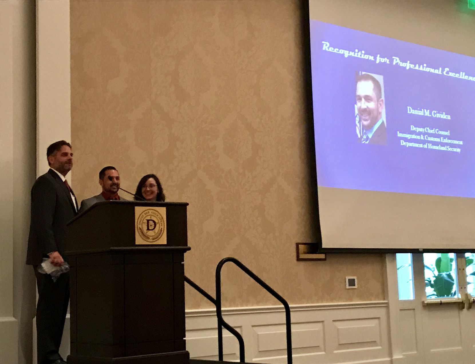 David Metzler (left) and Angela Lopez stand with Danial Gividen, the deputy chief counsel of ICE's Dallas regional office, who was recognized for professional excellence at the  Dallas Bar Association luncheon.
