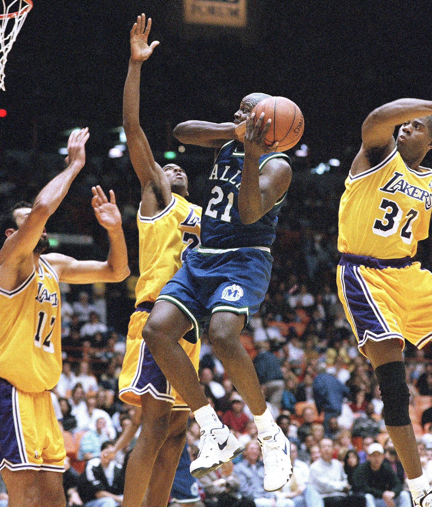 Dallas Mavericksí George McCloud attempts to pass Los Angeles Lakers, from left Vlade Divac, Eddie Jones and Earvin ìMagicî Johnson during second quarter action in Inglewood, California on Friday, Feb. 16, 1996. The Lakers defeated the Mavericks 119-114. (AP Photo/Michael Caulfield)