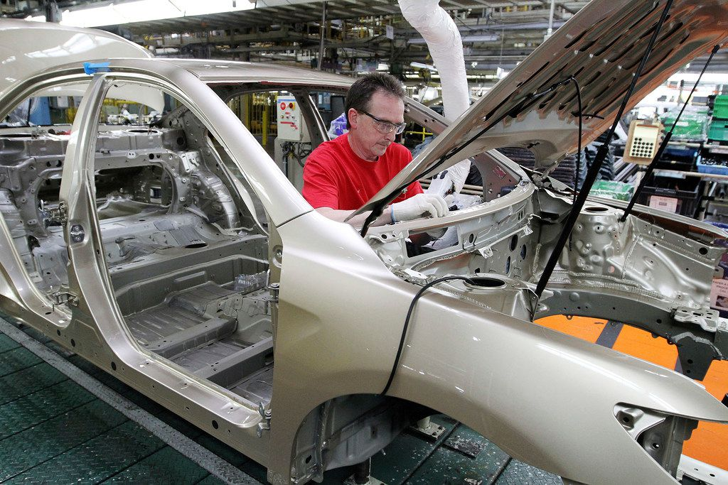 Production team member Darryl Ashley installs an inner dash silencer in a Camry on the assembly line at the Toyota Motor Manufacturing plant in Georgetown, Ky.