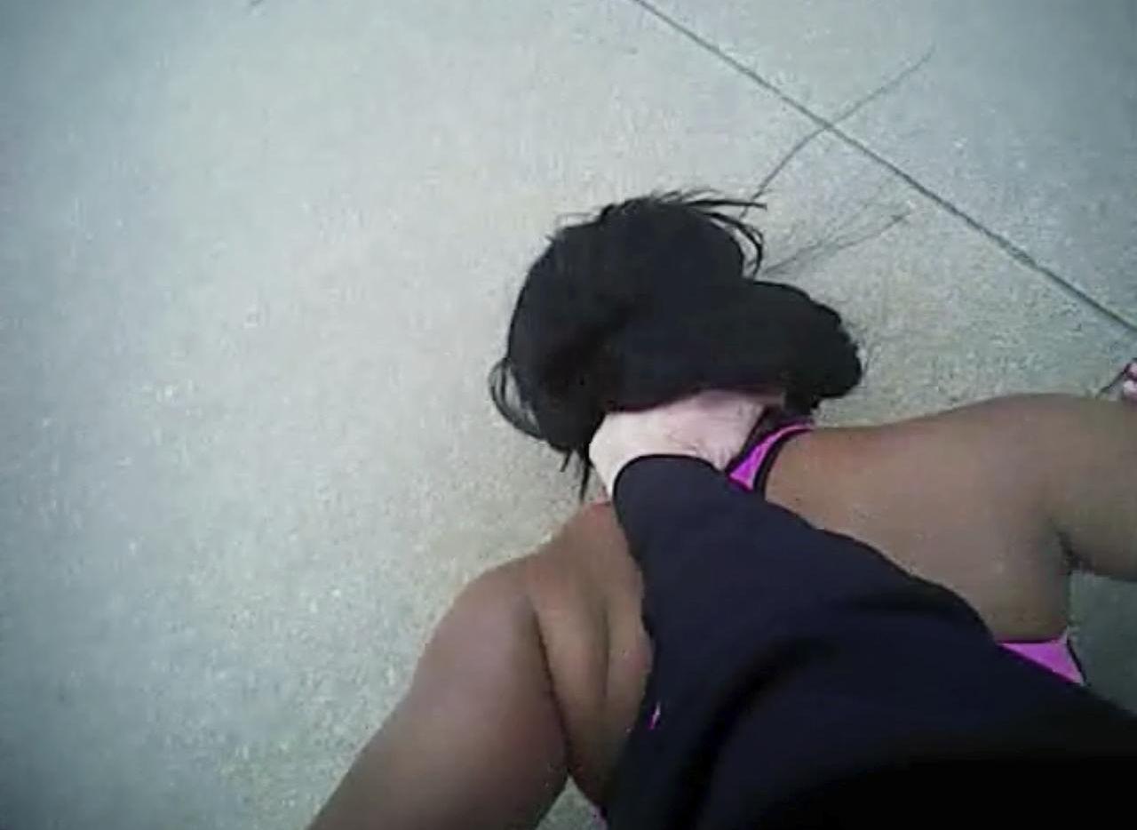 La imagen tomada de la cámara corporal del policía William Martin muestra cómo el policía sostiene contra el piso a la hija adolescente de Jacqueline Brown. (AP/FWPD)