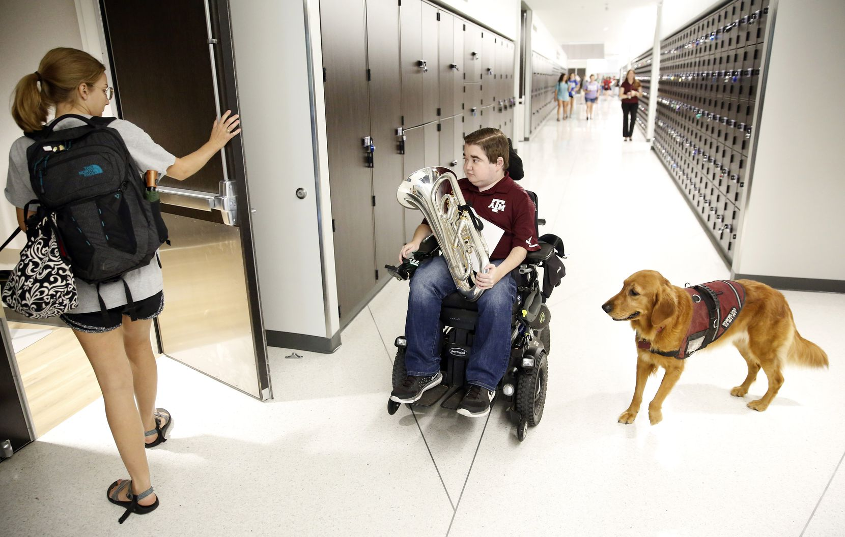 Texas A&M graduate student Kyle Cox, who has Duchenne muscular dystrophy, and his golden retriever service dog head to symphonic band rehearsal at the Music Activities Center on the Texas A&M campus in College Station on Sept. 11, 2019.