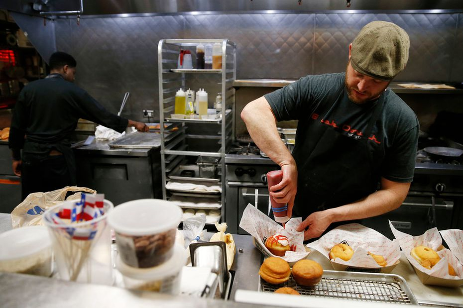 """Pastry chef Justin Biggs works on making a """"John Lennon"""" doughnut at Back Dough of Queenie's Steakhouse in Denton."""