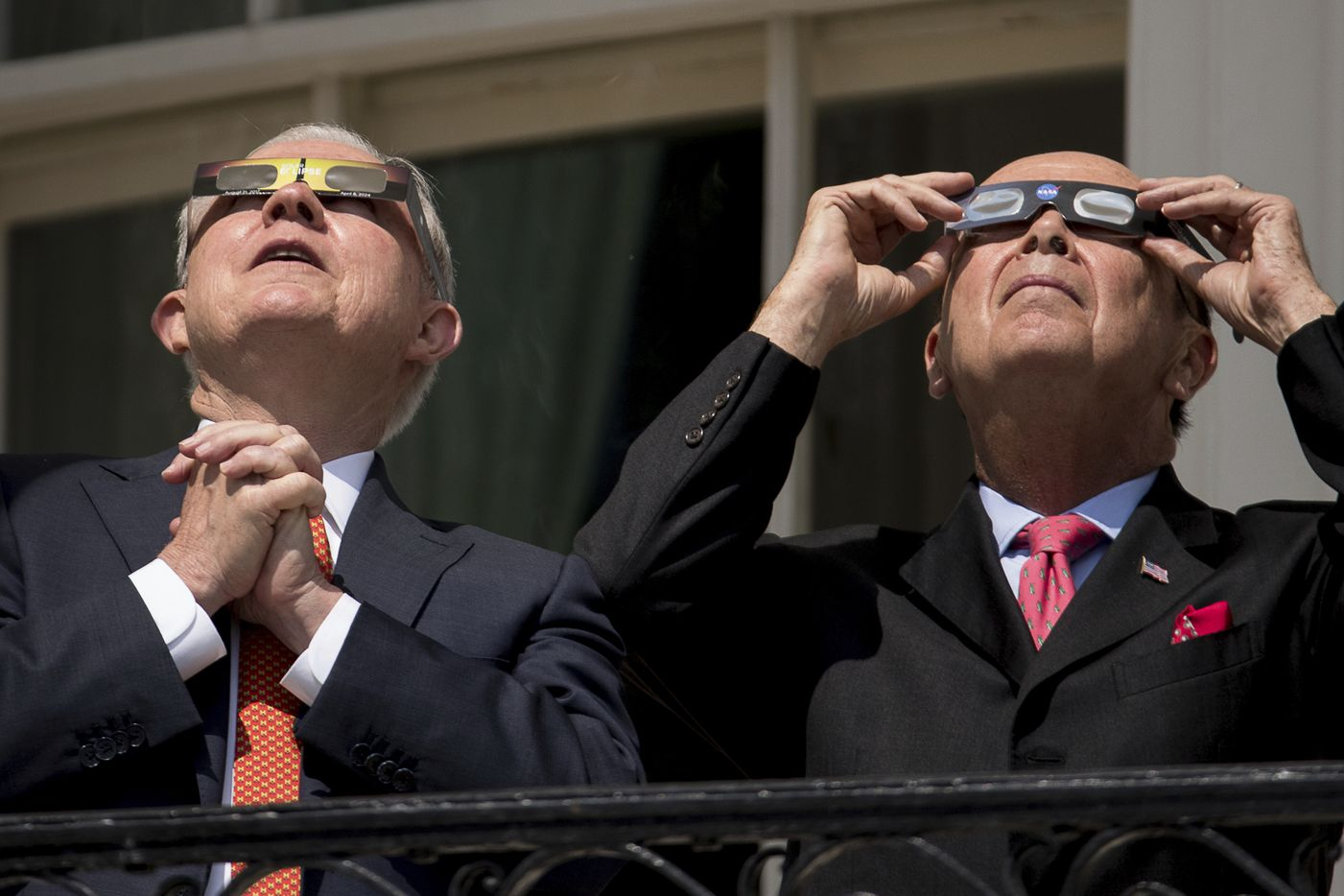 Attorney General Jeff Sessions, left, and Commerce Secretary Wilbur Ross wear protective glasses as they view the solar eclipse at the White House.