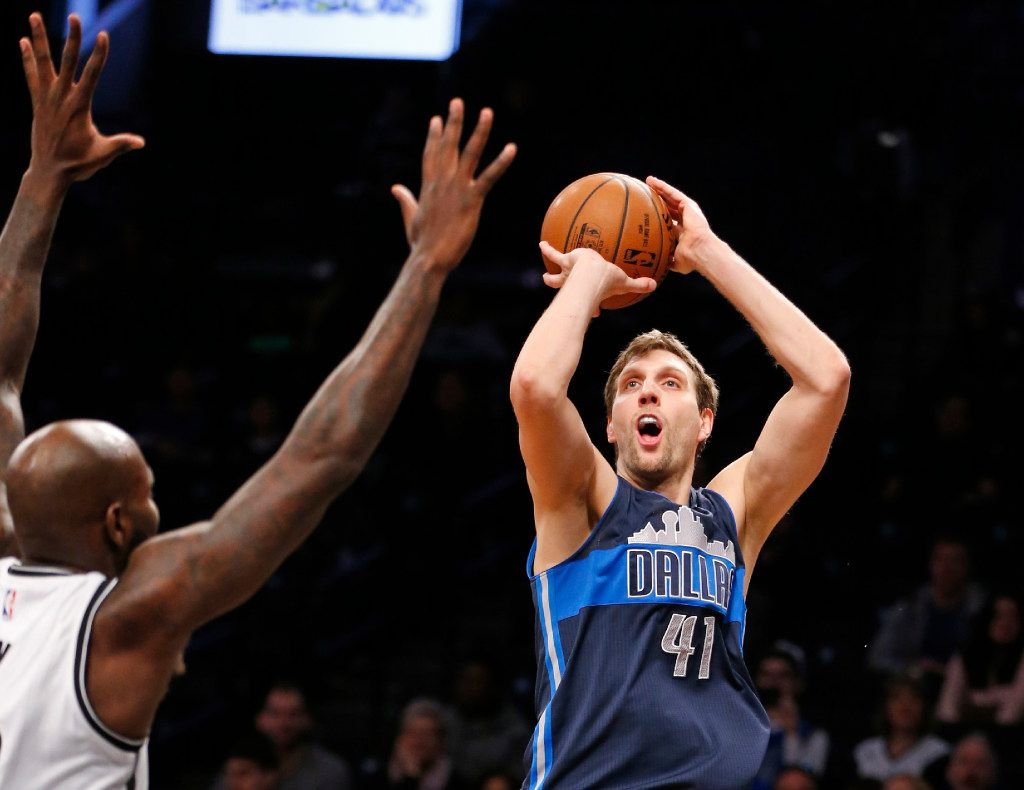Brooklyn Nets forward Quincy Acy (13) defends as Dallas Mavericks forward Dirk Nowitzki (41) shoots in the first half of an NBA basketball game, Sunday, March 19, 2017, in New York. (AP Photo/Kathy Willens)