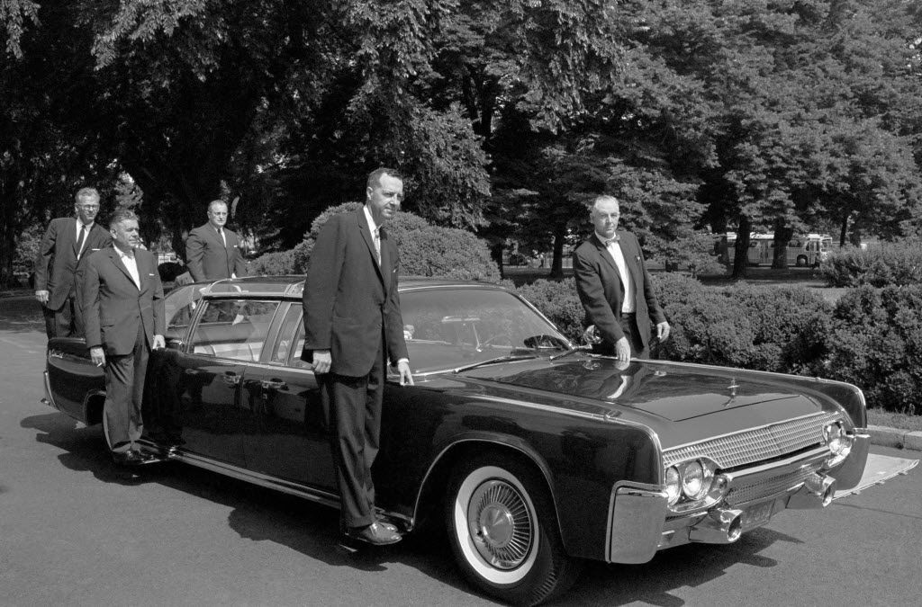 In June, 1961, U.S. Secret Service agents pose on retractable stands on President John F. Kennedy's new plastic-topped Lincoln Continental limousine outside the White House, after its delivery in Washington.  The car has three roof combinations, a rear seat that can be raised and lowered, retractable foot stands for Secret Service men, two two-way radio telephones, and a master control panel for power accessories.