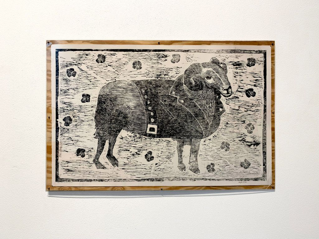 "Angela Faz's Black Ram With Pansies, a 2019 relief woodcut carved from plywood, references the gay slur ""pansy"" by portraying a ram in a leather jacket on a field of black pansies. The work turns the insult into an image of strength."