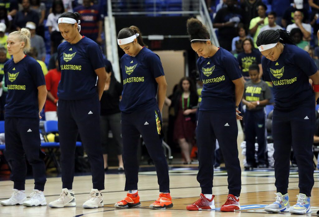 """From left to right, Dallas Wings' Erin Phillips,  Plenette Pierson, Skylar Diggins, Brianna Kiesel and Odyssey Sims bow their heads during a moment of silence before a WNBA basketball game against the Minnesota Lynx on Sunday, July 17, 2016, in Arlington, Texas. The Wings wore shirts with the slogan """"Dallas Strong"""" in observance of recent events where five Dallas police officers lost their lives. (AP Photo/Tony Gutierrez)"""