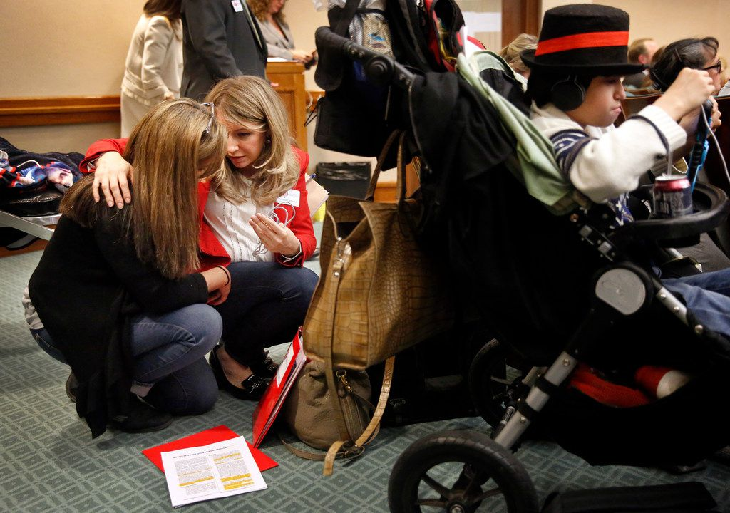 Hannah Mehta of Protect Fragile TX Children (center, right) comforts mother Gabriella McCann of Bulverde, Texas after she testified on behalf of her medically fragile son, Briar, on House Bill 2453 during the House Human Services Committee in early April. Mehta's medically fragile son Aiden plays video games in his stroller.