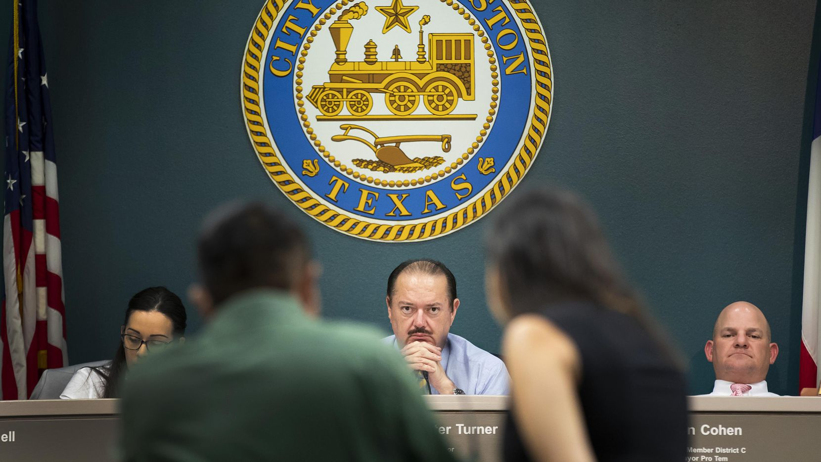 State Rep. Rene Oliveira (center), chairman of the Texas House Business and Industry Committee, listens as Ana Gonzalez, a policy advocate for Workers Defense Project (right), translates for worker Agustin Villanueva as he testifies about wage theft at a committee meeting at Houston City Hall on July 24, 2018, in Houston.