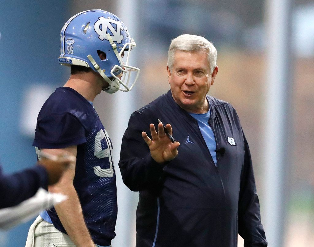FILE - In this March 3, 2019, file photo, North Carolina head coach Mack Brown talks with Cooper Graham (96) during UNC's first spring football practice, in Chapel Hill, N.C. Brown is savoring his return to coaching in a second stint with the Tar Heels. Brown had worked in broadcasting in the years since his departure from Texas after the 2013 season. But he says the time away rejuvenated him for his chance to return to the sideline. Now he's trying to stabilize a UNC program that has won two Atlantic Coast Conference games over the past two seasons. (Ethan Hyman/The News & Observer via AP, File)