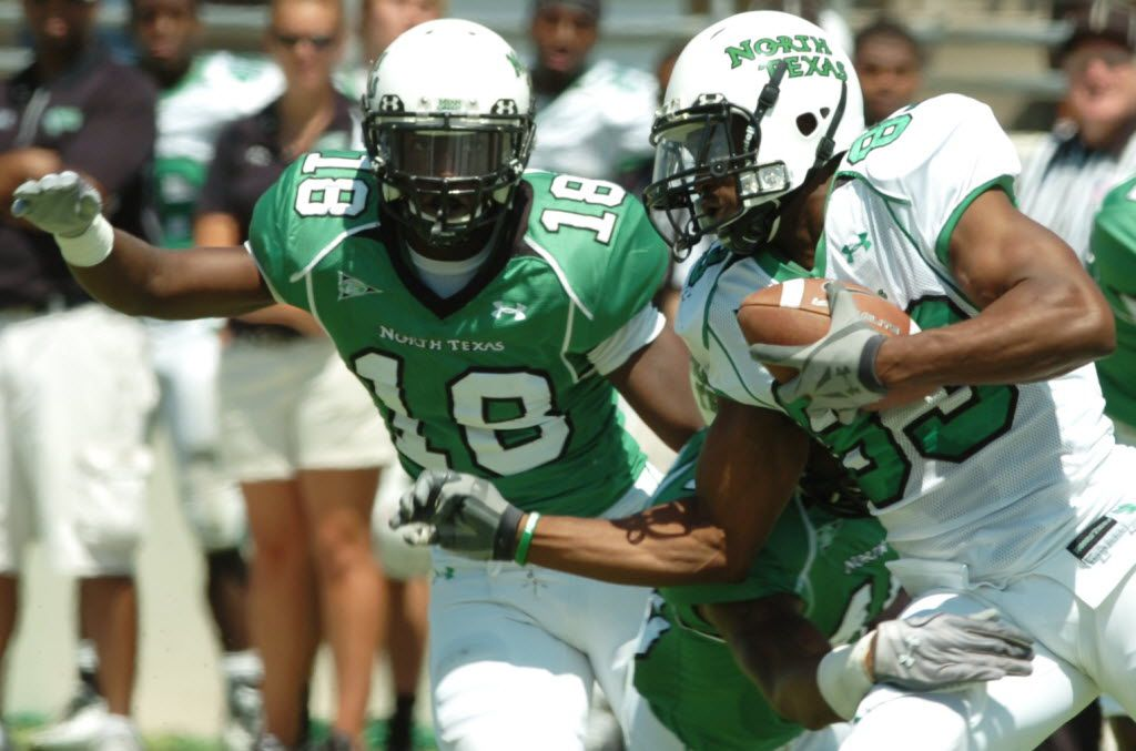 White team Wide reciever Jamize Olawale (83) shakes off a hit by Green linebacker Will Wright (40) ahead of Green defensive back John Shorter (18) University of North Texas football Spring Game, Saturday, April 16, 2011, at C.H. Collins Athletic Complex in Denton.