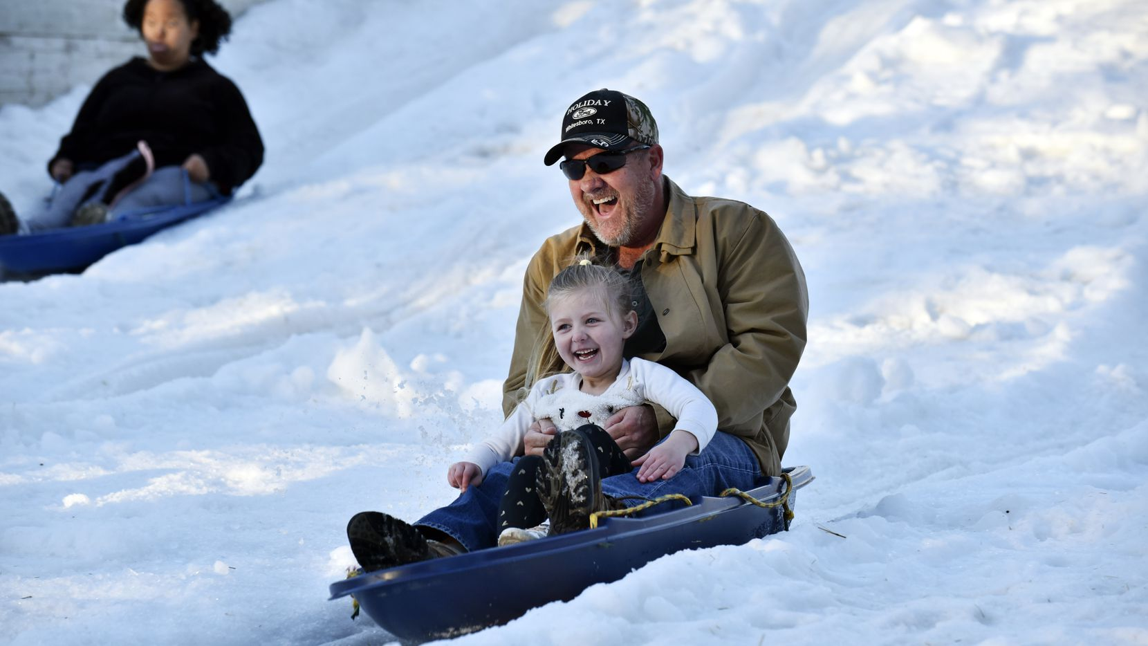 Rodney Allison and his granddaughter ride down a hill made of fake snow at The Frosty Snowhill during Six Flags Holiday in the Park.