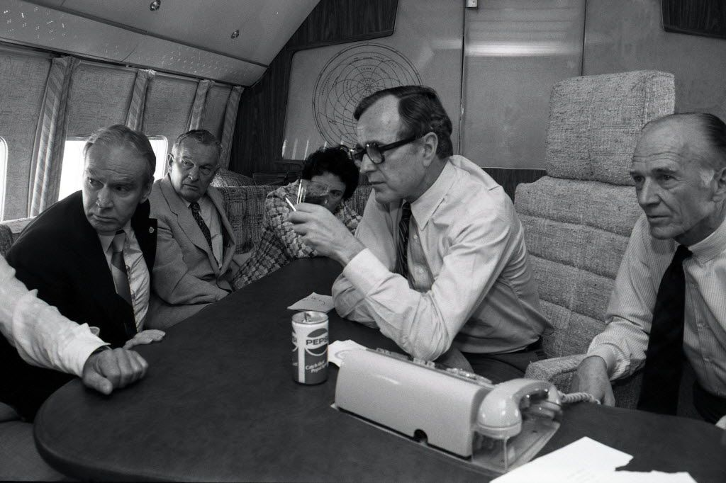 While Air Force Two refuels in Austin, Vice President George H.W. Bush watches the TV replay of the shooting of Ronald Reagan with House Majority Leader Jim Wright, Texas Gov. Bill Clements and Rita Clements (on sofa). Dallas Congressman Jim Collins kneels on Bush's left. March 30, 1981.