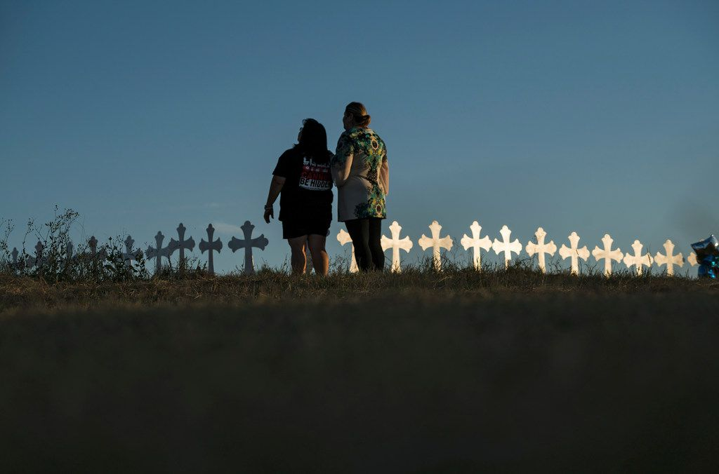 Sonia Yanez (left) and Laura Torres mourn near the 26 crosses set up for the victims killed in the Sutherland Springs church shooting. (Todd Heisler/The New York Times)