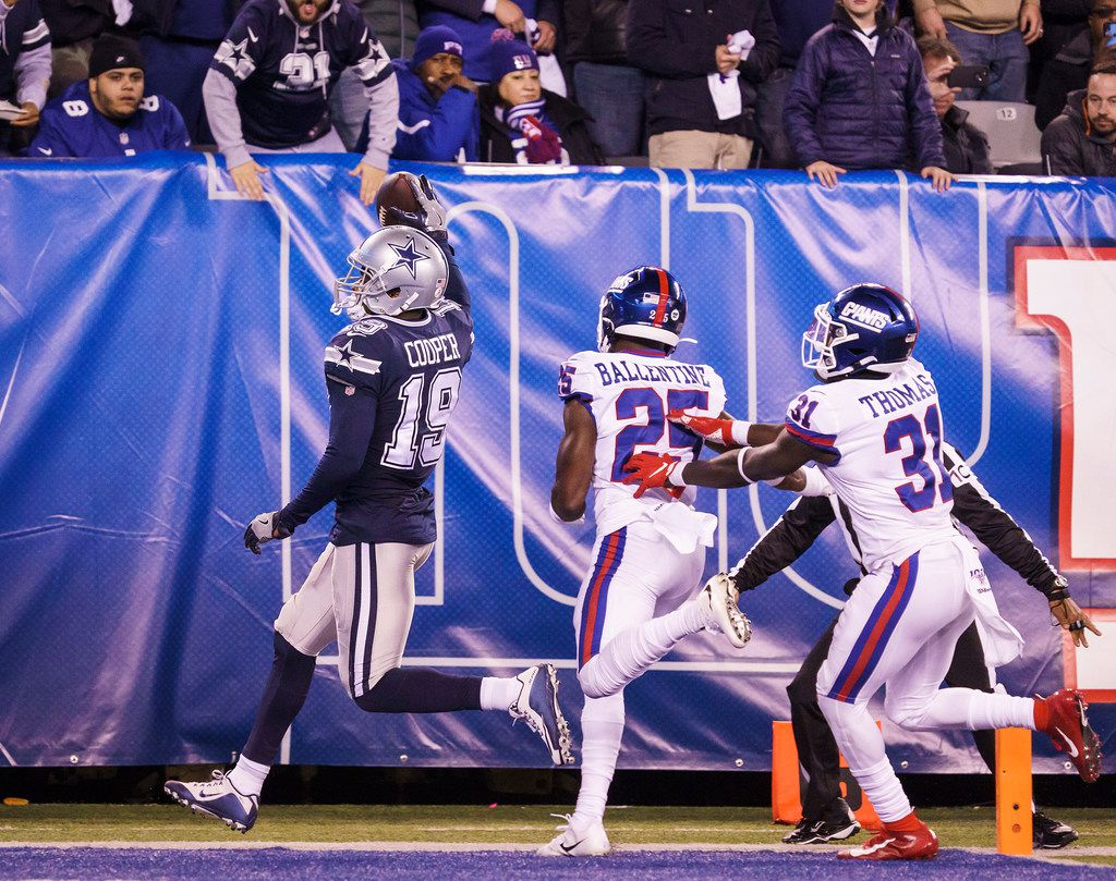 Dallas Cowboys wide receiver Amari Cooper (19) scores on a 45-yard touchdown past New York Giants defensive back Corey Ballentine (25) and defensive back Michael Thomas (31) during the second half of an NFL football game, Monday, Nov. 4, 2019, in East Rutherford, N.J. . (Smiley N. Pool/The Dallas Morning News)