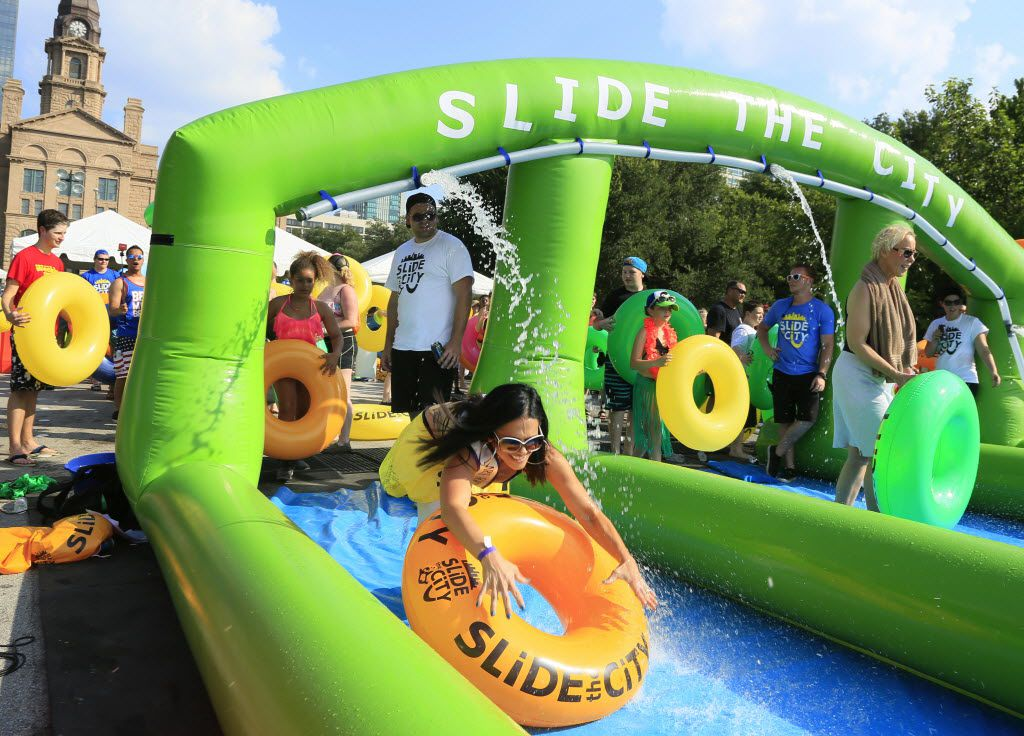 92.1 Hank FM morning show host Erin Wilde participates in an attempt to break the Guinness World Record for longest distance traveled on a water slide in one hour at a Slide the City event in Fort Worth.