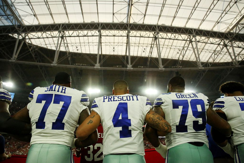 Dallas Cowboys quarterback Dak Prescott (4) locked arms with teammates during the playing of the national anthem before Monday's game against the Arizona Cardinals in Glendale, Ariz.