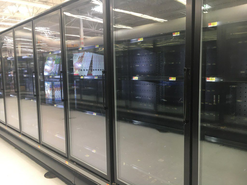 Freezer cases  sat  empty on Tuesday at the Walmart Supercenter on Samuell Boulevard in Far East Dallas. The store was forced to get rid of many of its refrigerated goods after Sunday's power outage.